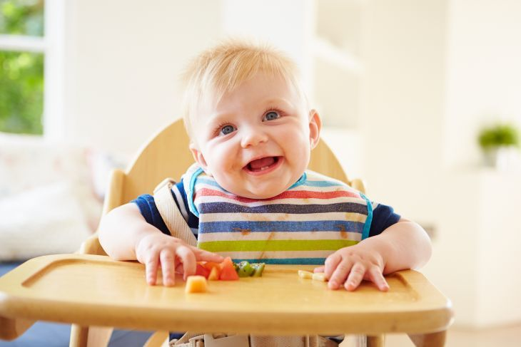 Cute baby boy wearing a bib while eating