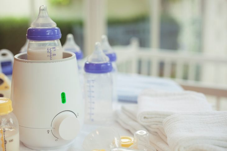 Baby bottle warmer on the kitchen counter warming a bottle of milk