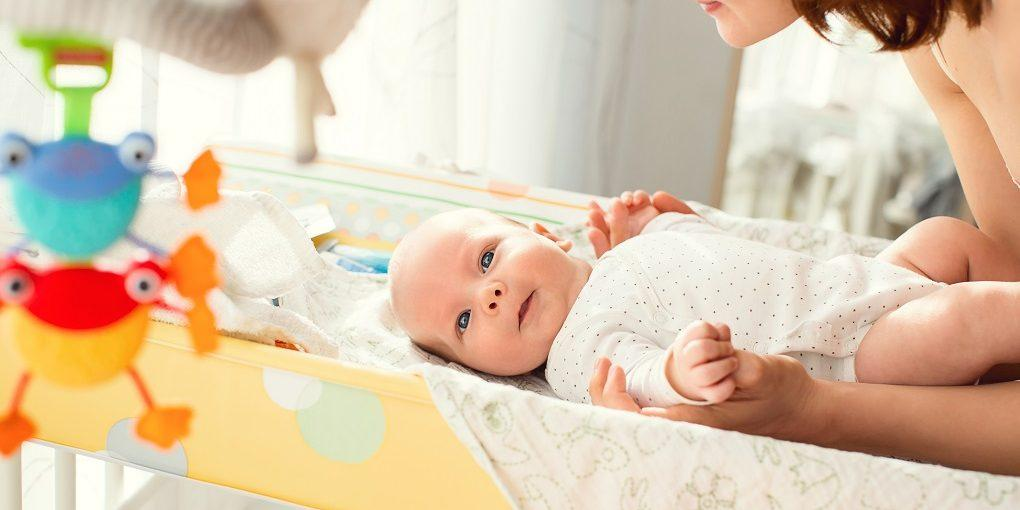 Baby having diaper changed on a changing table