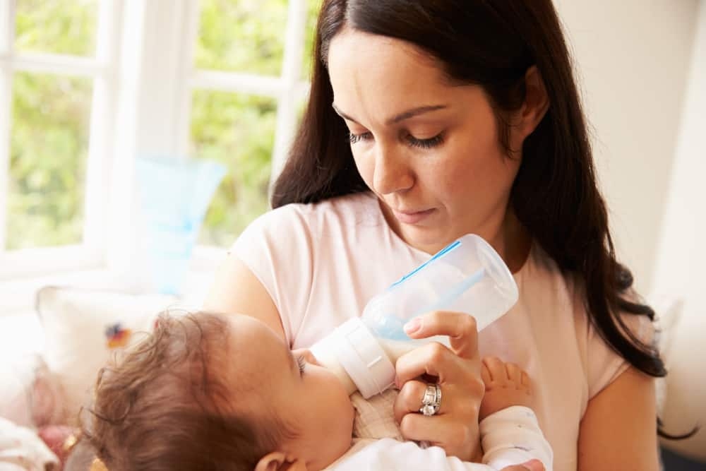 Mother feeding her baby with an anti-colic bottle