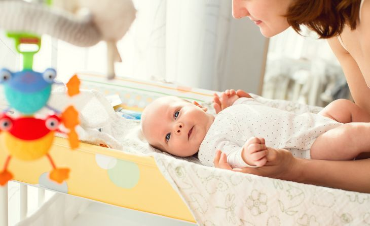 Mother changing baby's diaper on a changing table