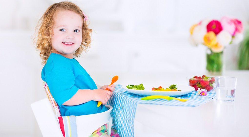 Toddler eating lunch sitting in a high chair
