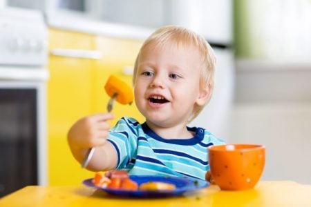 Toddler eating carrots sitting in a hook on high chair