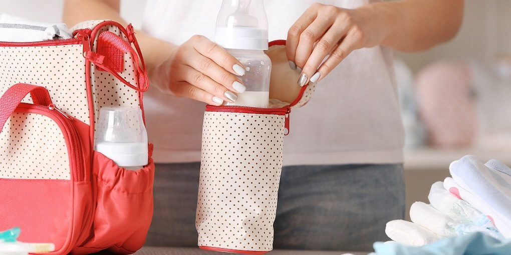 Woman packing her breast pump bag bag with child bottle