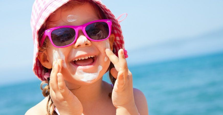 Young girl applying sunscreen to her face