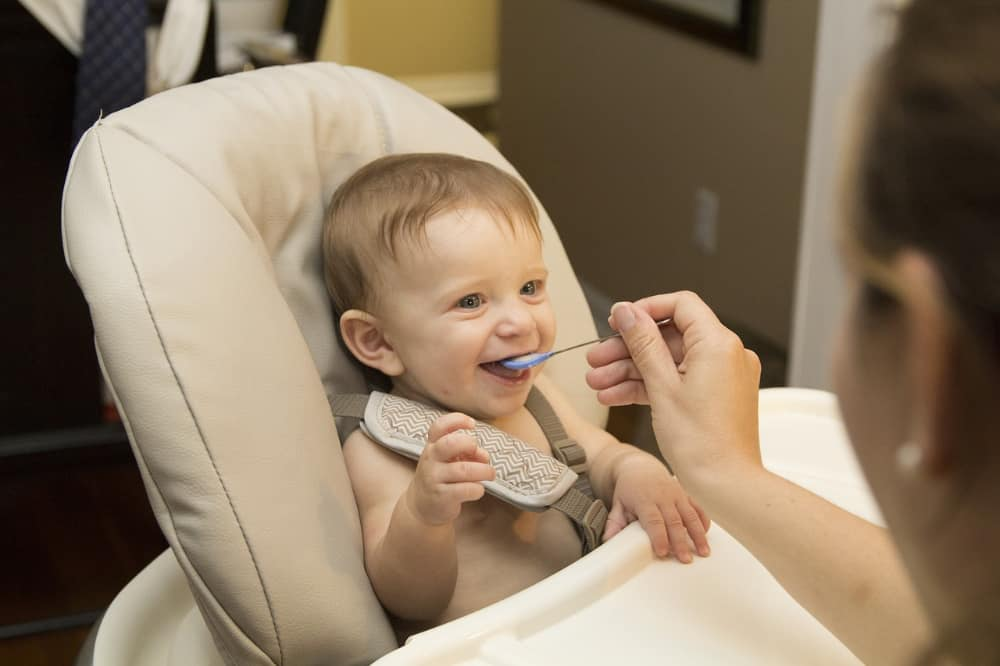 Baby eating sitting in high chair