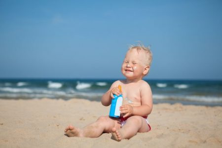 Baby on the beach wearing sunscreen