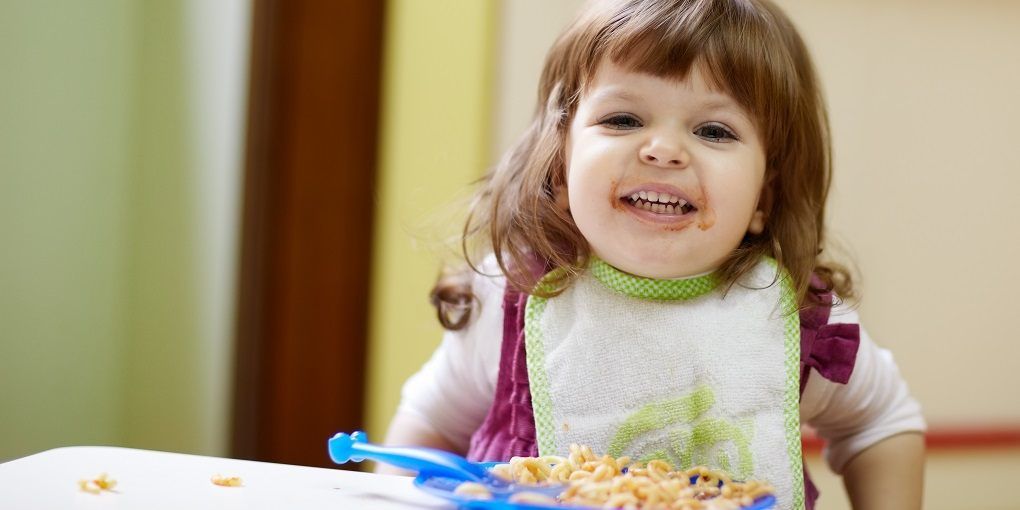 Little Girl Eating At Table Using A Booster Seat High Chair