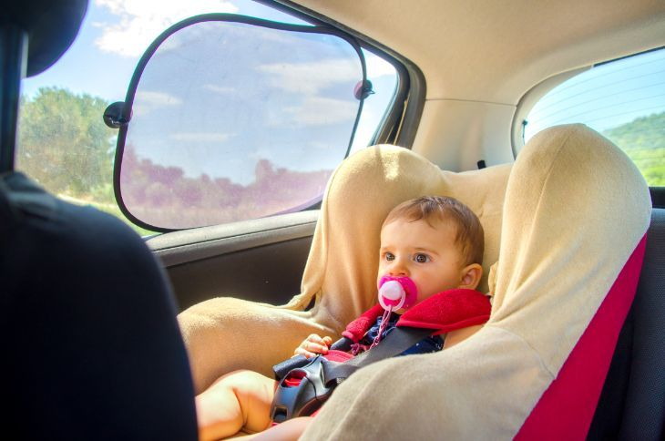 Baby sitting in car seat with sun protection from car sun shade