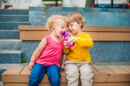 Toddlers drinking water from a reusable water bottle.