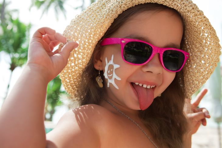 Baby girl wearing sunglasses on the beach