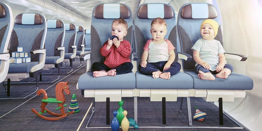 3 Baby sitting on the airplane waiting to travel