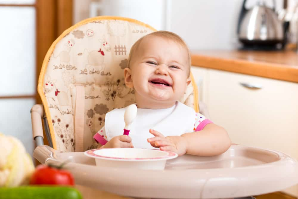 Baby eating in a booster seat in the kitchen