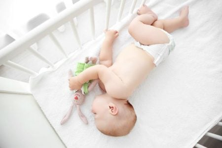 Newborn baby sleeping in a white crib