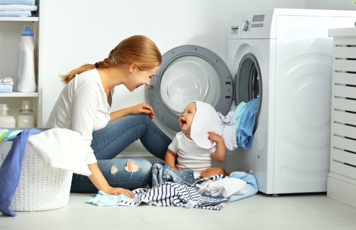 Mother and baby playing with clean laundry