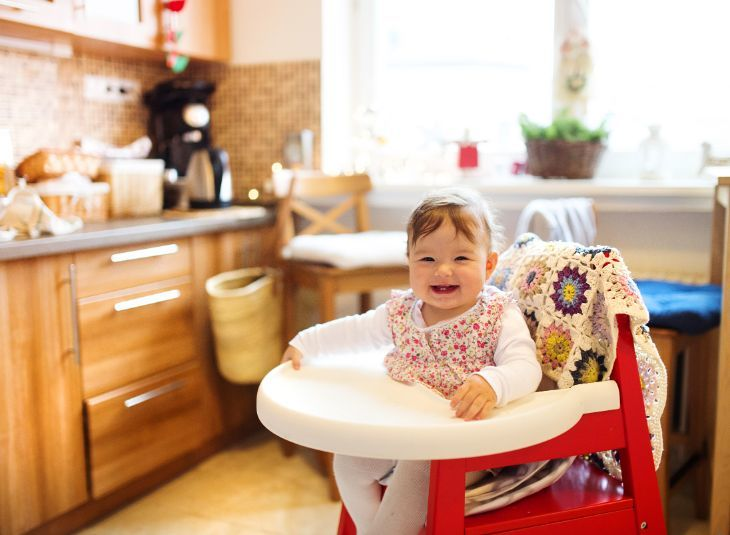 Baby girl sitting in a folding high chair