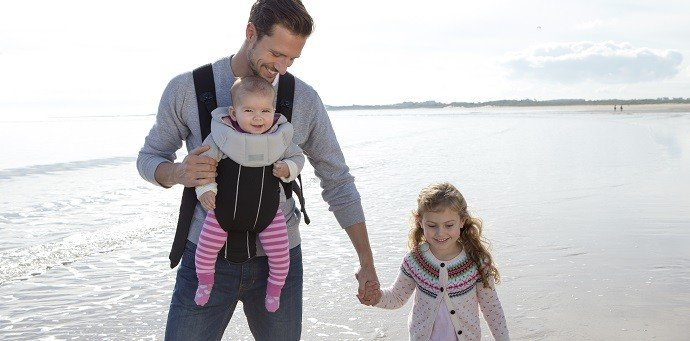 Father babywearing with daughter on the beach