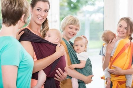 New mothers exercising wearing baby carriers