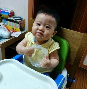 Messy Baby Eating in High Chair