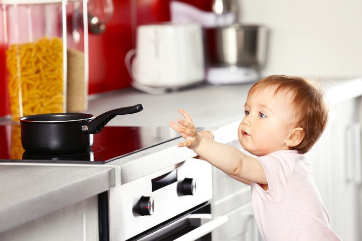 Young child touching a frying pan in the kitchen