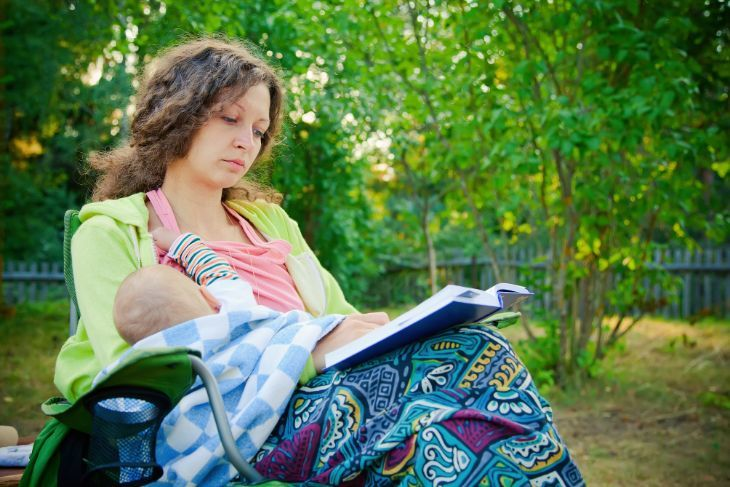 Mother breastfeeding her baby while reading a book