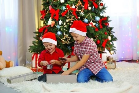Two young boys opening their Christmas gifts.