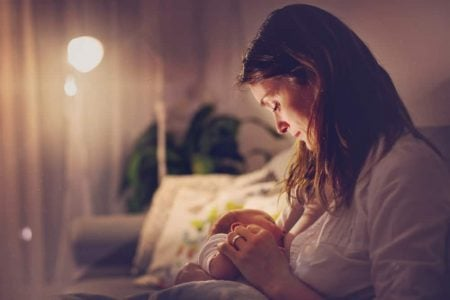 Woman breastfeeding her baby at night
