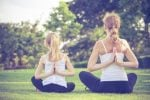 Mother and daughter practising yoga together