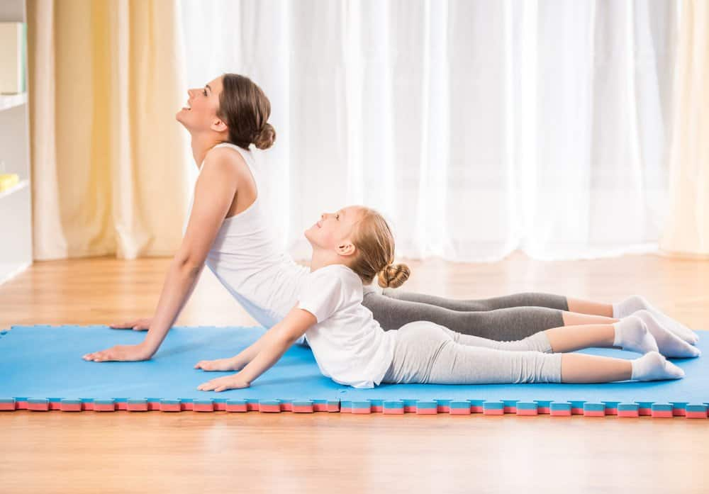 Mother and daughter doing yoga exercises on a mat