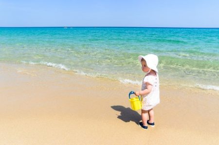 Baby wearing a sun hat on the beach