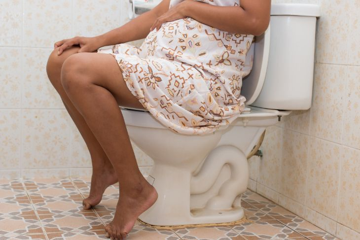 Pregnant woman sitting on the toilet with constipation