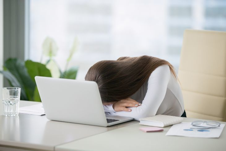 Woman taking a nap on the desk in front of her laptop