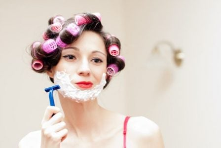 Pregnant woman wearing curlers shaving her face