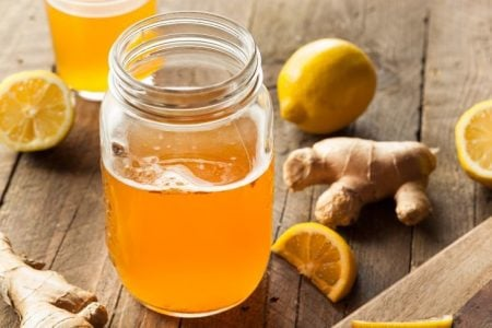 Kombucha on table with ginger and lemon