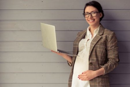 A smiling pregnant woman holding a laptop