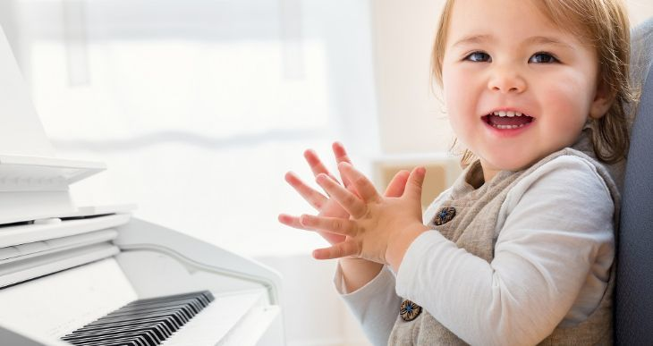 Happy toddler learning to play the piano