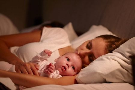 Mom sleeping with baby on the bed