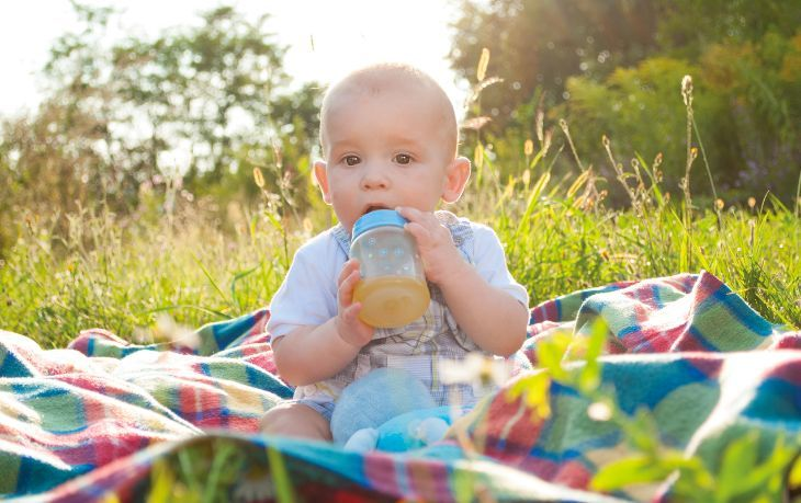 Baby drinking juice from a sippy cup