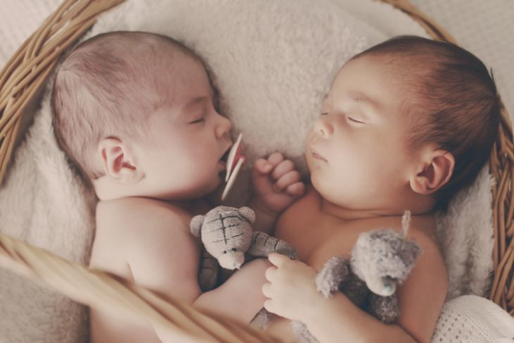 Twins sleeping together in a crib