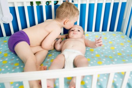Toddler kissing baby brother in crib
