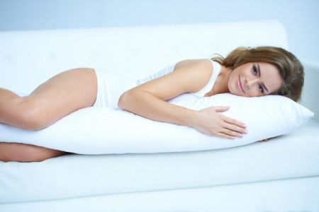 Woman laying on her side with a pregnancy pillow between her legs