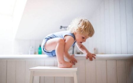 Toddler climbing into the bathtub unsupervised