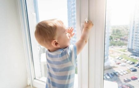 Toddler playing by the window unsupervised