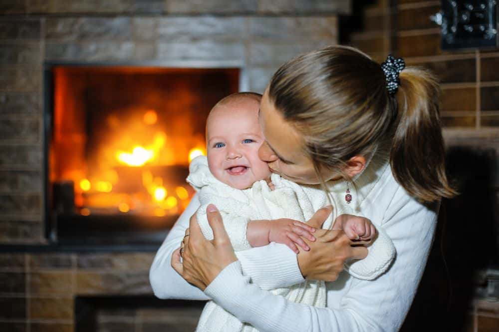 Mother kissing her baby by the fireplace