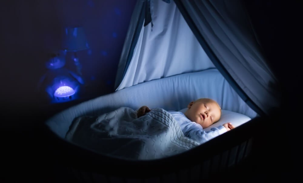 Mother breastfeeding in the nursery with a night light