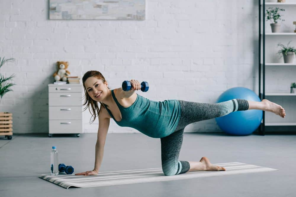 Pregnant woman exercising on a mat with weights