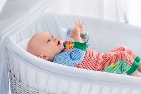 Baby lying inside a bassinet while holding a bottle