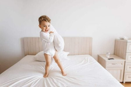 Toddler playing on the bed