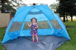 Baby girl standing in a beach tent