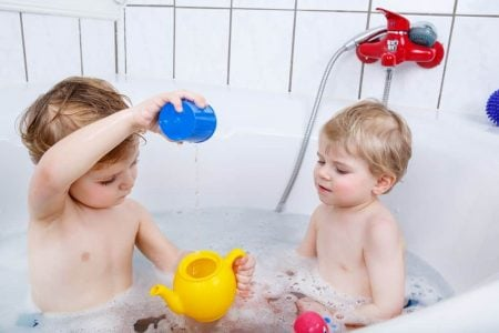 Two toddlers playing in the bathtub